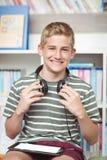 Retrato del colegial feliz con la tableta digital y los auriculares que se sientan en biblioteca Foto de archivo libre de regalías