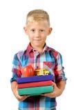 Retrato del colegial feliz con los libros y de la manzana aislada en el fondo blanco Educación Imagen de archivo libre de regalías