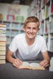 Retrato del colegial feliz que miente en piso con los libros en biblioteca Imagen de archivo