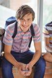 Retrato del colegial feliz que se sienta en travesaño de la ventana y que usa el teléfono móvil en pasillo Foto de archivo