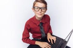 Retrato del colegial positivo y emocional que presenta con el ordenador portátil, mecanografiando en el teclado, fondo blanco, vi Imágenes de archivo libres de regalías