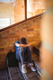 Retrato del colegial que sostiene la tableta y el libro digitales cerca de escalera Foto de archivo