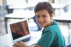 Retrato del colegial que usa el ordenador portátil en sala de clase Foto de archivo