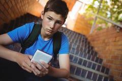 Retrato del colegial que usa el teléfono móvil en escalera Fotos de archivo libres de regalías