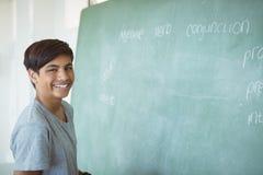 Retrato del colegial sonriente que coloca la pizarra cercana en sala de clase Imagenes de archivo