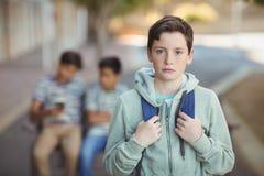 Retrato del colegial triste con la cartera que se coloca en campus Imagen de archivo