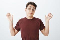 Retrato del compañero de trabajo masculino europeo inconsciente descuidado en vidrios y camiseta redondos, aumentando las palmas  foto de archivo
