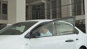Retrato del comprador que se sienta en el coche y que examina el salón almacen de metraje de vídeo