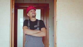 Retrato del constructor adulto joven hermoso barbudo alegre en fondo de un apartamento renovado metrajes