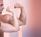 Retrato del constructor de carrocería con el músculo i del bíceps Foto de archivo