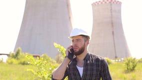 Retrato del constructor en casco y teléfono al aire libre almacen de metraje de vídeo