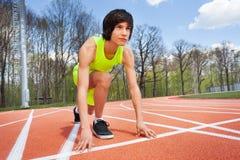 Retrato del corredor en la posición de comienzo lista para competir con Fotos de archivo libres de regalías