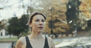 Retrato del corredor femenino moreno atractivo que corre en auriculares de los auriculares del bluetooth de los airpods del parqu almacen de metraje de vídeo