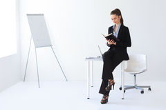 Retrato del cuaderno hermoso de la lectura de la mujer de negocios en apagado fotografía de archivo