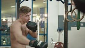 Retrato del culturista muscular hermoso con el torso desnudo que encajona un saco de arena en el gimnasio moderno 4K almacen de metraje de vídeo