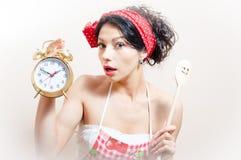 Retrato del delantal que lleva de la muchacha modela morena hermosa divertida de la mujer que sostiene el despertador y la cuchara Fotos de archivo