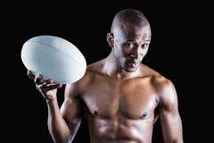 Retrato del deportista descamisado confiado que sostiene la bola de rugbi Imagen de archivo libre de regalías