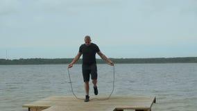 Retrato del deportista muscular que ejercita con la cuerda de salto afuera en el lago almacen de metraje de vídeo