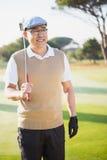 Retrato del deportista que detiene a su club de golf y que mira lejos Fotos de archivo libres de regalías