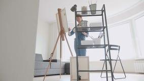 Retrato del dibujo caucásico de la mujer joven en el caballete en el estudio casero Movimiento lento de la cámara del allanamient almacen de metraje de vídeo