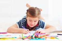 Retrato del dibujo feliz lindo de la muchacha, mientras que pone en la alfombra imagenes de archivo