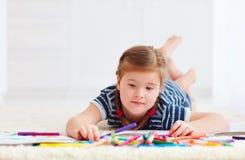 Retrato del dibujo feliz lindo de la muchacha, mientras que pone en la alfombra foto de archivo libre de regalías