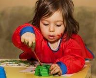 Retrato del dibujo lindo y de estudiar del pequeño niño en la guardería Imagenes de archivo