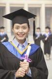 Retrato del diploma que se sostiene graduado de la hembra joven en un vestido y un birrete de la graduación Foto de archivo libre de regalías
