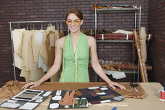 Retrato del diseñador de moda bastante de sexo femenino que se coloca en la tabla con las disposiciones Fotografía de archivo