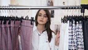 Retrato del diseñador de moda de sexo femenino joven que mira en el nuevo propia colección de paño en el estante de la ropa metrajes