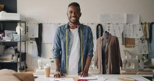 Retrato del diseñador de ropa que mira la situación de la cámara en estudio con el maniquí almacen de metraje de vídeo