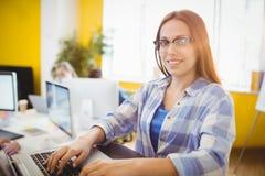 Retrato del diseñador gráfico de sexo femenino sonriente que trabaja con el ordenador portátil Imagen de archivo