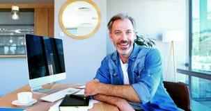 Retrato del diseñador gráfico que se sienta en el escritorio almacen de video