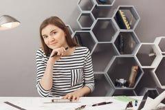Retrato del diseñador independiente de sexo femenino oscuro-cabelludo alegre joven que se sienta en la tabla en espacio de co-tra fotografía de archivo libre de regalías