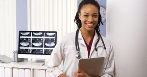 Retrato del doctor afroamericano de la mujer que sonríe en hospital Imágenes de archivo libres de regalías