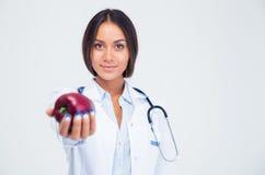 Retrato del doctor de sexo femenino lindo que da la manzana en la cámara imágenes de archivo libres de regalías