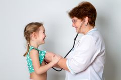 Retrato del doctor de sexo femenino que escucha los childs que respiran usando el estetoscopio Fotos de archivo