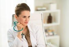 Retrato del doctor de sexo femenino que se sienta en un escritorio en la oficina Imágenes de archivo libres de regalías