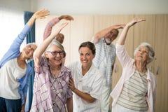 Retrato del doctor de sexo femenino sonriente que ayuda al ejercicio mayor de la mujer Foto de archivo