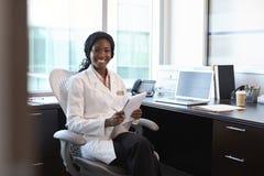 Retrato del doctor de sexo femenino Wearing White Coat en oficina Fotografía de archivo libre de regalías