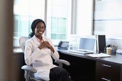 Retrato del doctor de sexo femenino Wearing White Coat en oficina Imagen de archivo