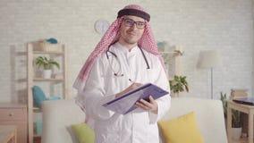 Retrato del doctor de sexo masculino árabe que sonríe y que mira la cámara almacen de video