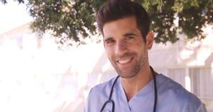 Retrato del doctor de sexo masculino que sonríe en el patio trasero metrajes