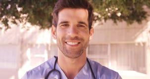 Retrato del doctor de sexo masculino que sonríe en el patio trasero almacen de metraje de vídeo