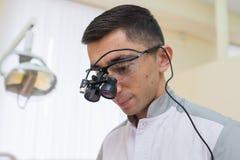 Retrato del doctor joven con las lupas binoculares dentales en su cara en la clínica del dentista Fotografía de archivo libre de regalías