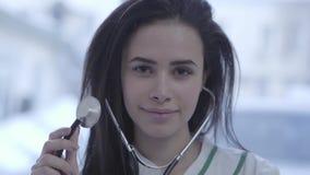 Retrato del doctor joven sonriente bonito cercano para arriba Mujer linda con el pelo moreno largo que mira in camera que se sost almacen de metraje de vídeo
