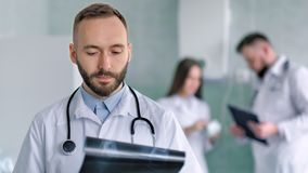 Retrato del doctor masculino de sexo masculino con el estetoscopio que revisa foto de la radiografía almacen de metraje de vídeo