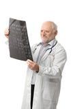 Retrato del doctor mayor que mira imagen de la radiografía Imágenes de archivo libres de regalías