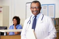 Retrato del doctor At Nurses Station fotos de archivo
