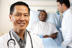 Retrato del doctor With Patient In Background Imagenes de archivo